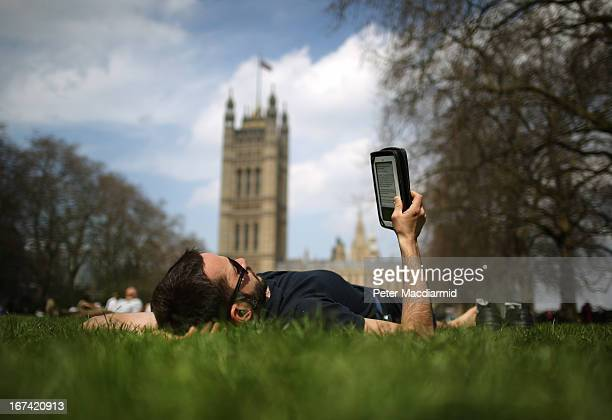 A man reads an ebook in Victoria Tower Gardens on April 25 2013 in London England Following an unseasonably cold start to 2013 higher temperatures...