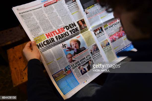 A man reads an issue of Gunes a Turkish progovernment daily newspaper with on an inside page German Chancellor Angela Merkel depicted in Nazi uniform...