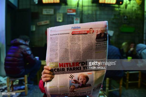 Man reads an issue of Gunes, a Turkish pro-government daily newspaper, with on an inside page German Chancellor Angela Merkel depicted in Nazi...