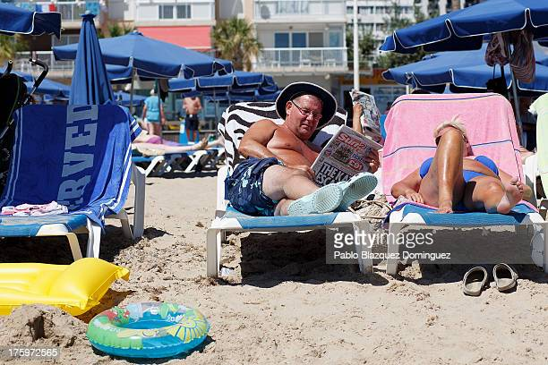 A man reads British newspaper The Sun on Levante Beach on August 10 2013 in Benidorm Spain Benidorm is one of Europe's top package holiday...