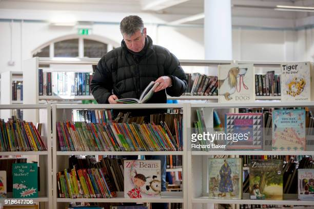 A man reads childrens' titles in the reopened Carnegie Library on Herne Hill in south London which has opened its doors for the first time in almost...