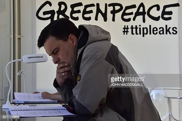 A man reads classified papers from the ongoing USEU trade talks presented to the public by Greenpeace in a glas container near the Brandenburger Gate...