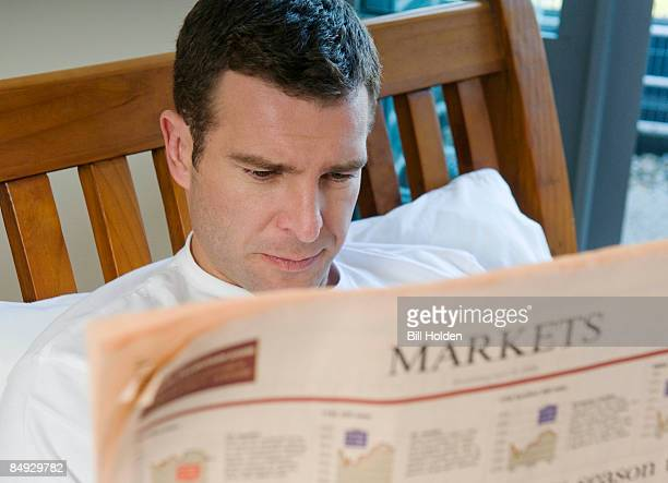 Man reads financial paper in bed