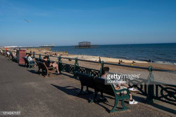 Man reads his book from a beach bench in Brighton, a seaside resort in the county of East Sussex. It is a constituent part of the city of Brighton...