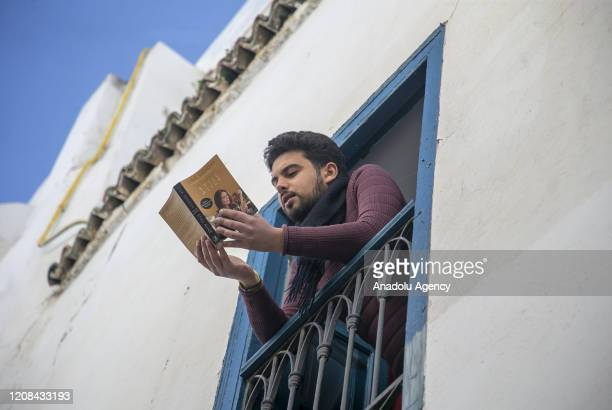 Man reads his book on his window after partial curfew declaration within precautions against coronavirus pandemic in Tunisia's old city Al Madina...