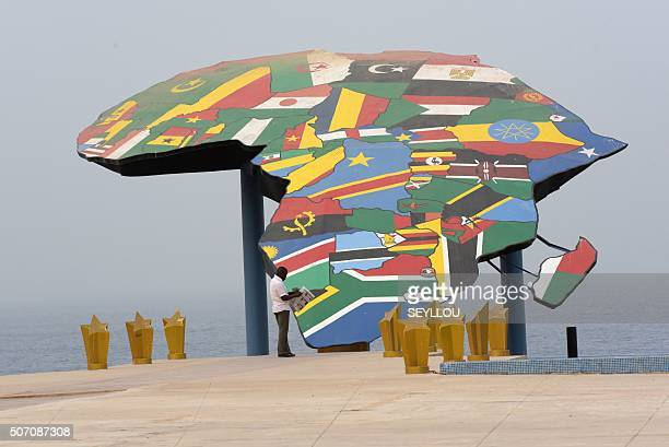 A man reads his newspaper in front a map of Africa at the Place du Souvenir Africain in Dakar on January 27 2016 / AFP / SEYLLOU