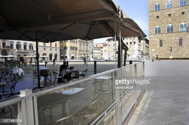 Man reads in a bar in an almost empty Piazza della Signoria the day of the reopening of the Italian borders on June 3, 2020 in Florence, Italy. From...