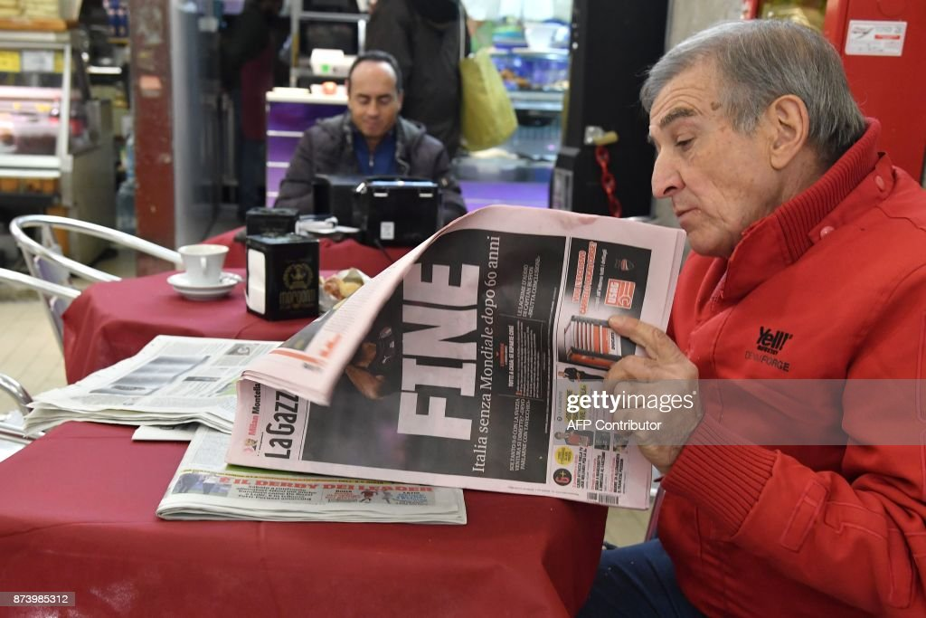A man reads Italian sport newspaper 'Gazetta dello Sport' with a front page reading 'End' a day after the elimination of Italy during the FIFA World Cup 2018 qualification football match against Sweden, on November 14, 2017 in a food market in Rome. Italy failed to reach the World Cup for the first time since 1958 on Monday as they were held to a 0-0 draw in the second leg of their play-off at the San Siro by Sweden, who qualified with a 1-0 aggregate victory. / AFP PHOTO / Tiziana FABI