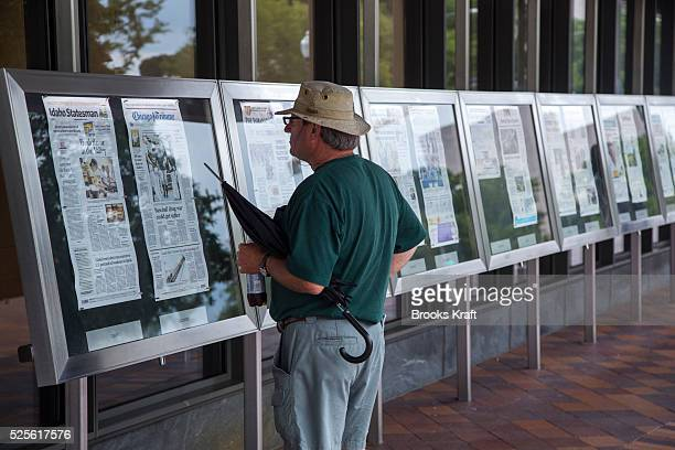 A man reads newspaper front pages outside the Newseum in Washington DC