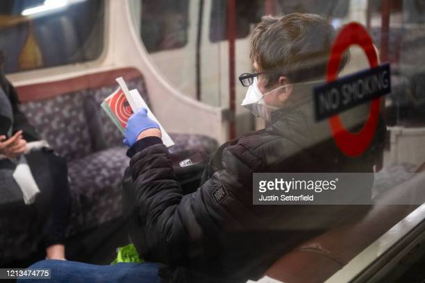 Man reads on the bakerloo line wearing a protective face mask and gloves on March 19, 2020 in London, England. Transport for London announced the...