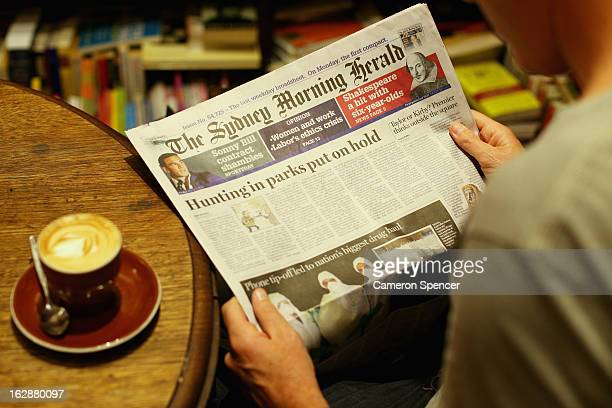 A man reads the broadsheet format 'Sydney Morning Herald' newspaper at a cafe on March 1 2013 in Sydney Australia After 180 years the Monday to...