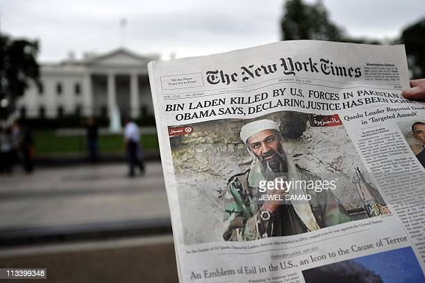 Man reads the front page of a newspaper featuring a picture of Al-Qaeda leader Osama bin Laden, in front of the White House in Washington, DC, on May...
