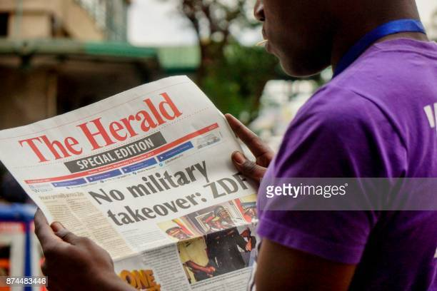 A man reads the front page of a special edition of The Herald newspaper about the crisis in Zimbabwe with the headline 'No military takeover ZDF' on...