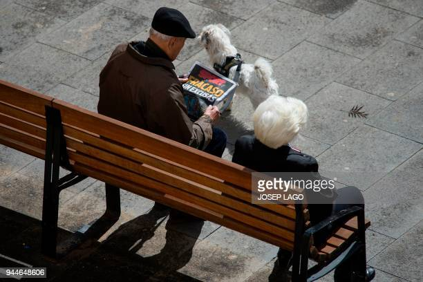 """Man reads the front page of a sport newspaper reading """"Failure without excuses"""" in Barcelona on April 11, 2018 a day after the victory of AS Roma..."""