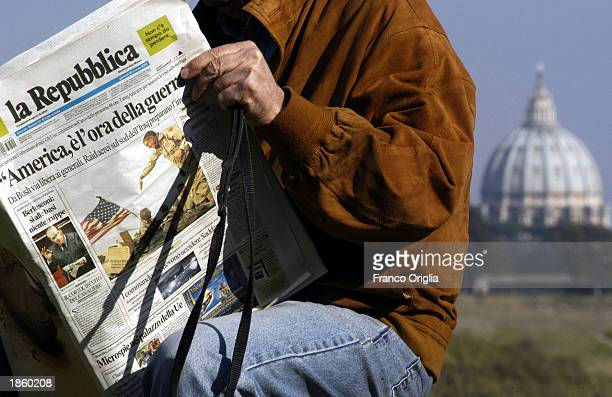 """Man reads the Italian newspaper """"La Repubblica"""" March 20, 2003 in Rome, Italy. Behind him rises the cupola of St. Peter's basilica."""