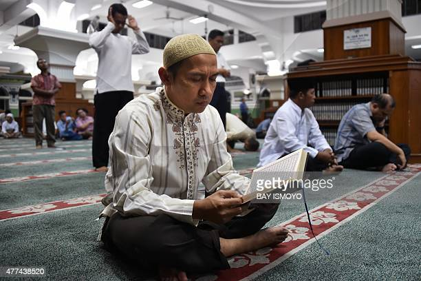 A man reads the koran as Indonesian Muslims wait for the first day of Ramadan prayers at Alazhar Mosque in Jakarta on June 17 to mark the Muslim holy...