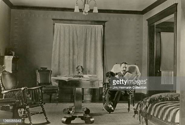 Man reads the newspaper in his living room with a black dog resting idly in his lap, circa 1899.