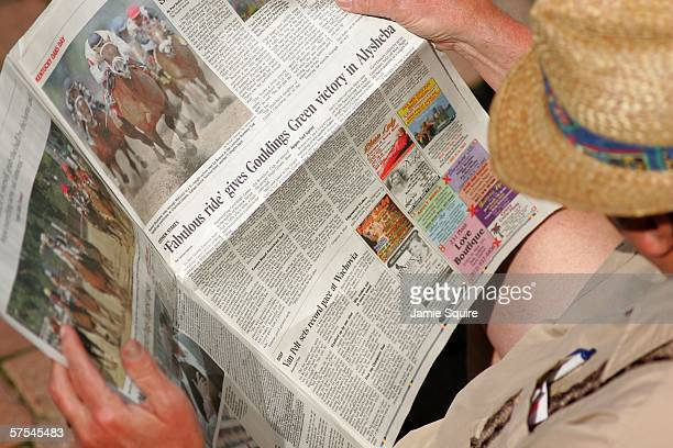 A man reads the newspaper in the paddock during the 132nd Kentucky Derby on May 6 2006 at Churchill Downs in Louisville Kentucky