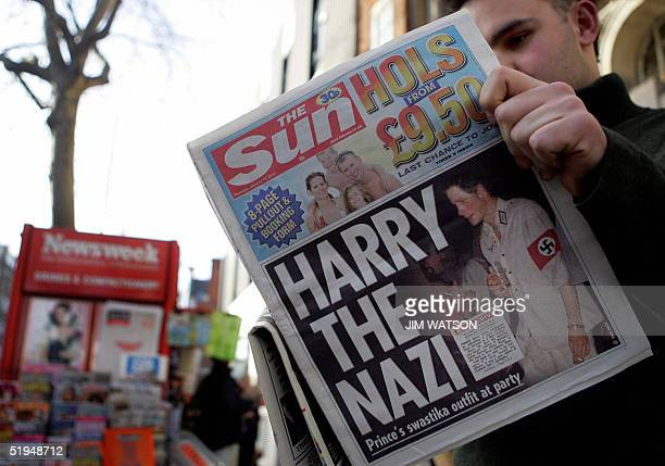 A man reads the newspaper The Sun in London 13 January 2005 with a headline about Prince Harry wearing a Nazi uniform at a costume party Britain's...