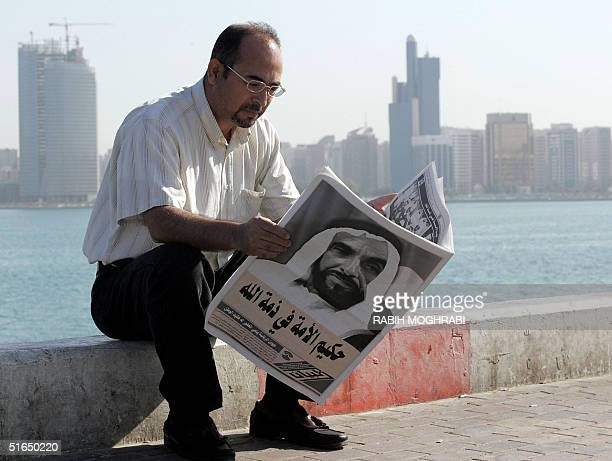 A man reads the newspapers with Sheikh Zayed bin Sultan alNahayan's portrait covering the whole front page during the funeral procession of the...