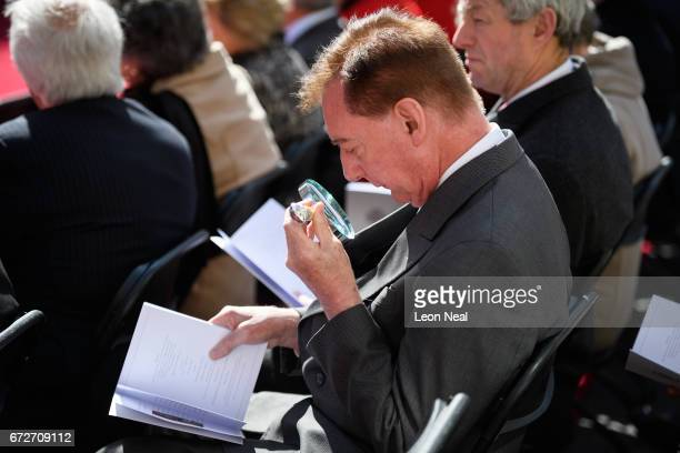 A man reads the order of service with a magnifying glass ahead of the unveiling of a monument outside the Freemasons' Hall listing the 64 servicemen...