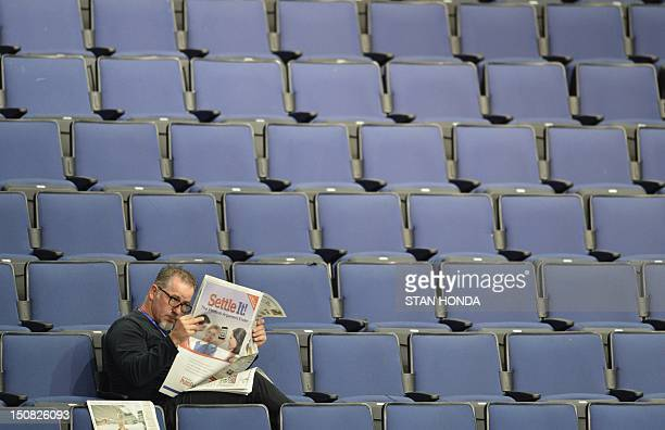 A man reads the paper sitting in the bleachers of the Tampa Bay Times Forum in Tampa Florida on August 27 2012 Due to Tropical Storm Isaac the...