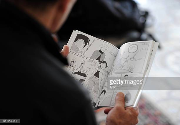 STORY A man reads 'The revolution' a manga comic book created by Algerian artist Fella Matougui for the 50th anniversary of Algeria's independence on...