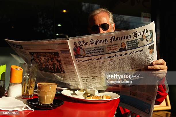 A man reads the Sydney Morning Herald newspaper on June 20 2012 in Sydney Australia Fairfax media group this week announced it will cut 1900 staff...