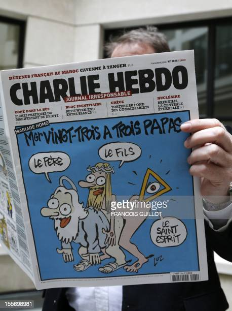 A man reads today's issue of the French satirical weekly newspaper Charlie Hebdo whose front page reads Archbishop VingtTrois has three fathers in...