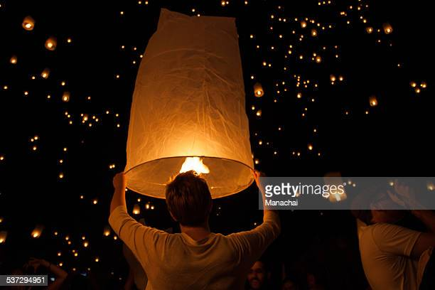 a man ready for release the lantern into the sky - yi peng stock pictures, royalty-free photos & images