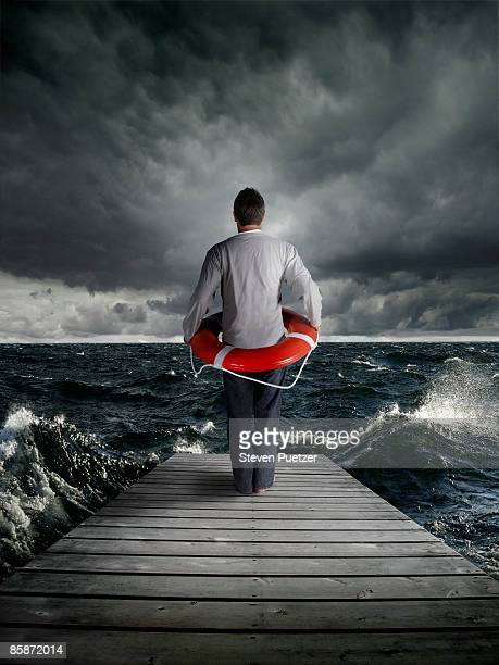 Man ready to jump off pier with life ring