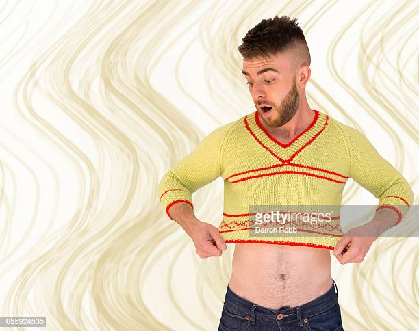 man realising his jumper has shrunk - small stock pictures, royalty-free photos & images
