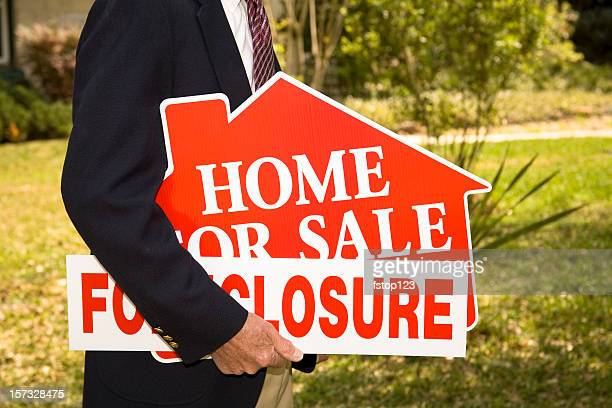 Man Realtor holds Foreclosure Real Estate Signs. Home.