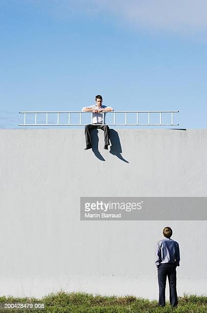 Man, rear view, looking up at man sitting on wall holding ladder