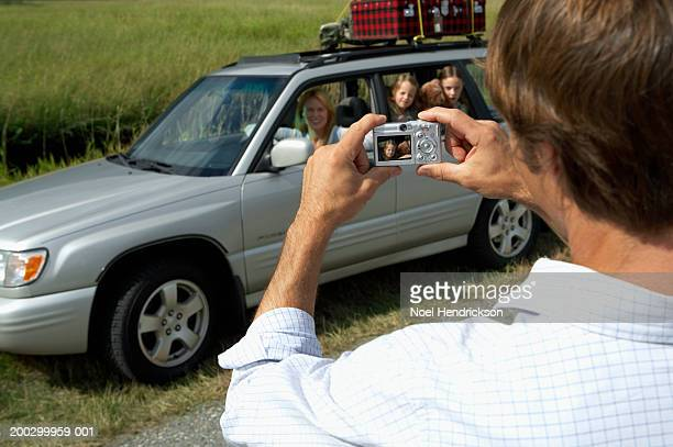 man, rear view, photographing woman and daughters (6-8 years) in car - 30 39 years photos et images de collection