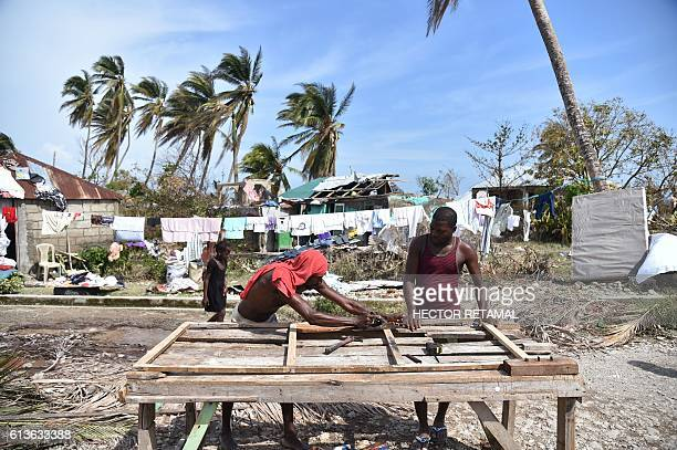 TOPSHOT A man rebuilds a a door for his house damaged by Hurricane Matthew in Sous Roche in the southwest of Haiti on October 9 2016 Haiti began...