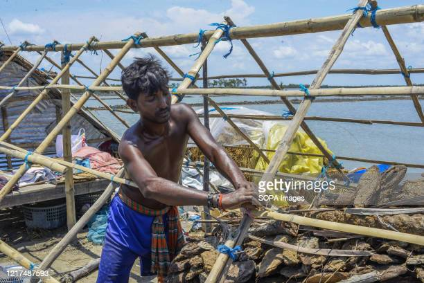Man rebuilds his house in the aftermath of the extremely severe cyclonic storm Amphan. Thousands of shrimp enclosures have been washed away, while...