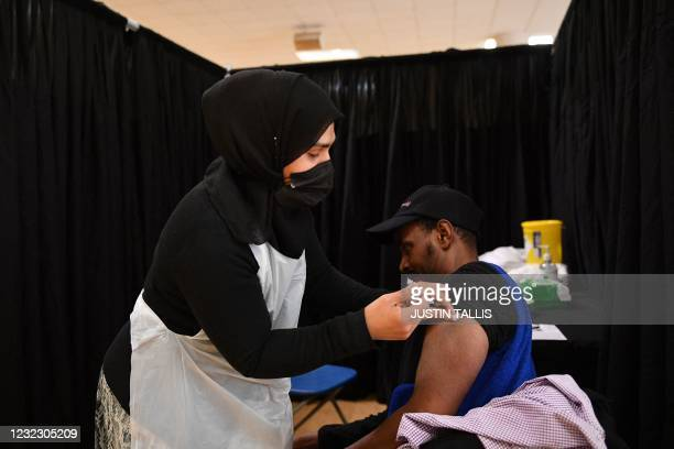Man receives a dose of the Astrazeneca/Oxford Covid-19 vaccine at a temporary vaccination centre set up at the East London Mosque in London on April...