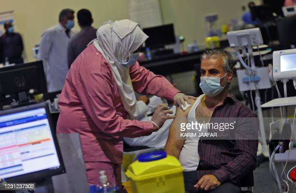 Man receives a dose of the COVID-19 vaccine at the Qatar National Convention Centre for mass vaccination in the capital Doha, on February 18, 2021. -...