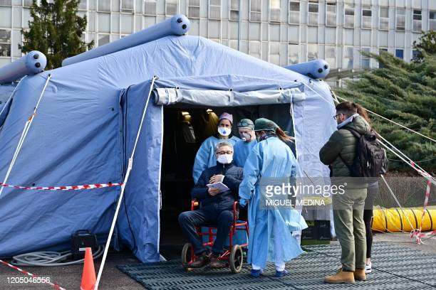 A man receives assistance in the a pretriage medical tent in front of the Cremona hospital in Cremona northern Italy on March 4 2020 Italy will...