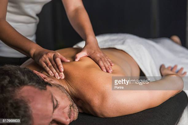 man receives back massage in spa - masajista fotografías e imágenes de stock