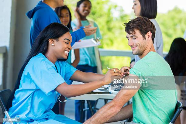 man receives immunization at outdoor free clinic - temporary stock pictures, royalty-free photos & images