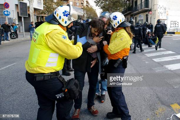 A man receives medical help after being dragged by Catalan regional policemen on a picket blocking the street at the bus North Station in Barcelona...