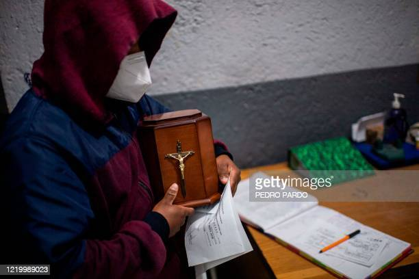 Man receives the urn containing the ashes of his father, a victim of COVID-19, at the crematorium of the Iztapalapa pantheon in Mexico City, on June...