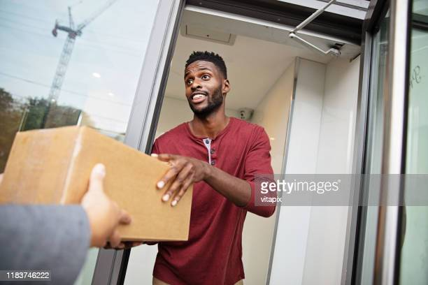man receiving a parcel - receiving stock pictures, royalty-free photos & images