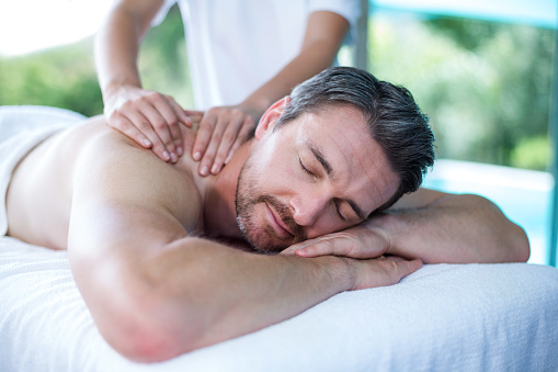 Man receiving back massage from masseur 673295102