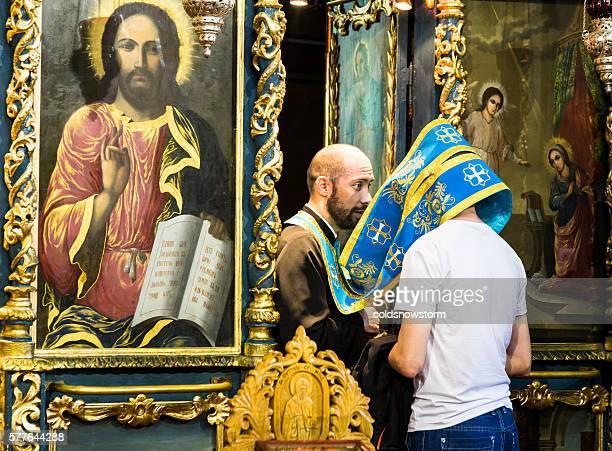 Man receiving confession in an orthodox church, Bucharest, Romania