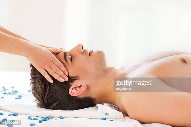 Hombre recibir masaje de cabeza en el spa.