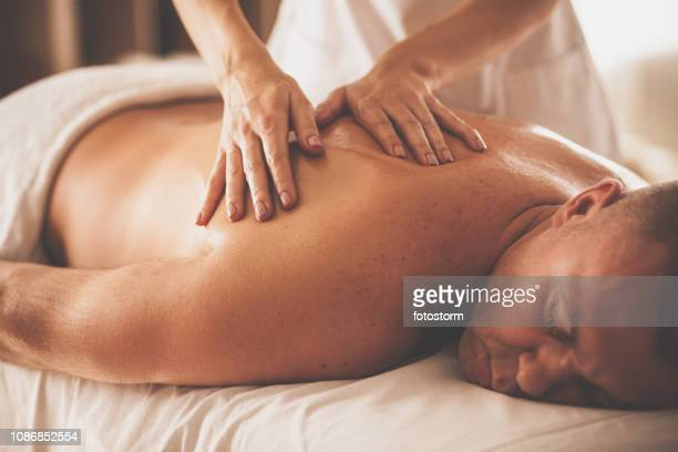 man receiving massage therapy at spa - foot massage stock pictures, royalty-free photos & images