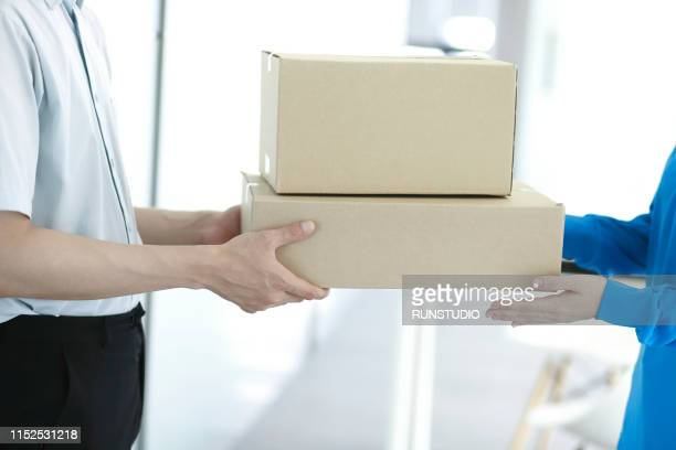 man receiving package from delivery man - 受ける ストックフォトと画像